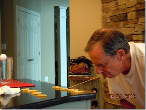Bill  sucessfulling putting ziti on a piece of spaghetti.