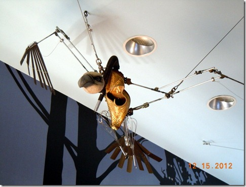An eagle made from a shoe, whisk, and blinds.