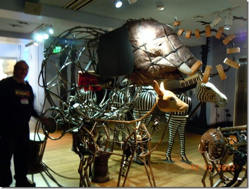 A elephant made from steel and Bob is turning a drum in the back.