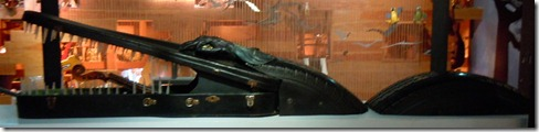 An alligator made from a violin case and tires.