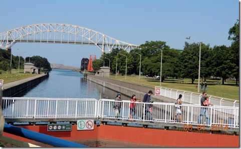 People crossing to the Canadian side of the lock, walking across top of lock.
